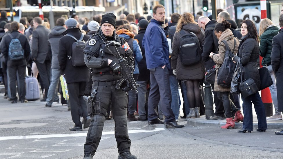 An armed police officer oversees queues of people waiting for a bus