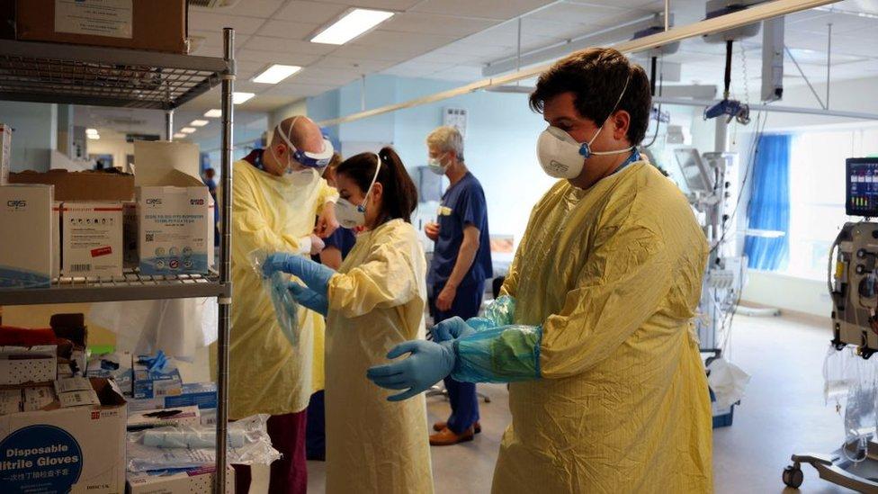 Trabajadores de la salud se preparan para recibir más pacientes en un hospital en Inglaterra