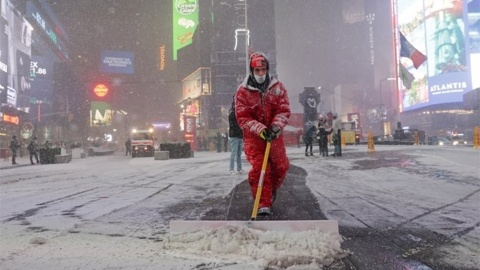 A worker clears snow in Times Square