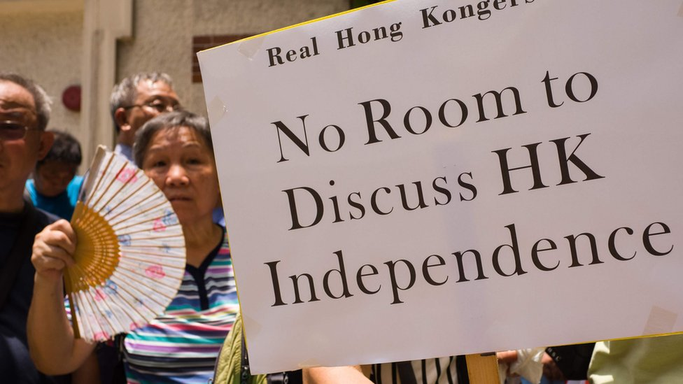 Protesters holding a banner 'Nor room to discuss HK independence'