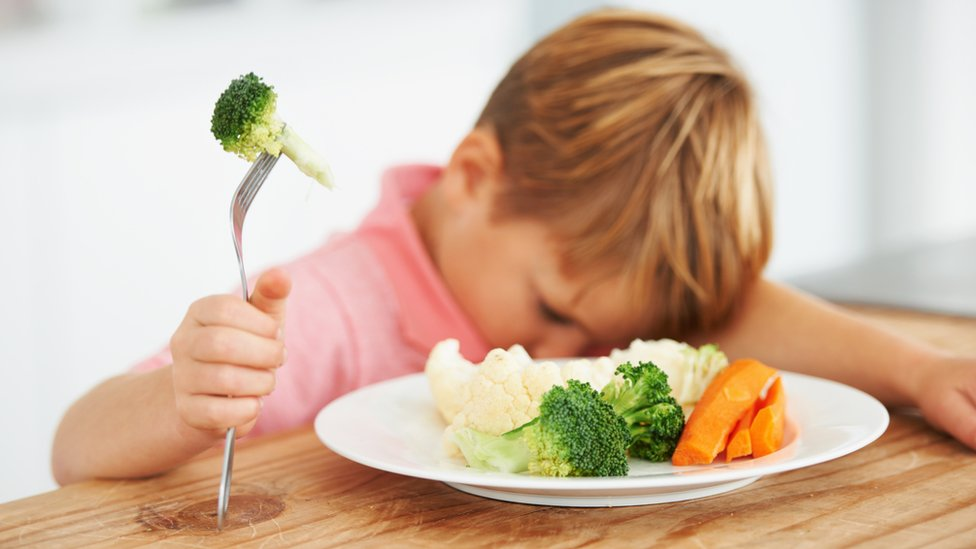 Un niño que no quiere comer verduras.