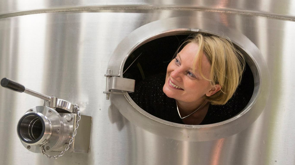 Floriane Eznack peeks out from a large silver tank