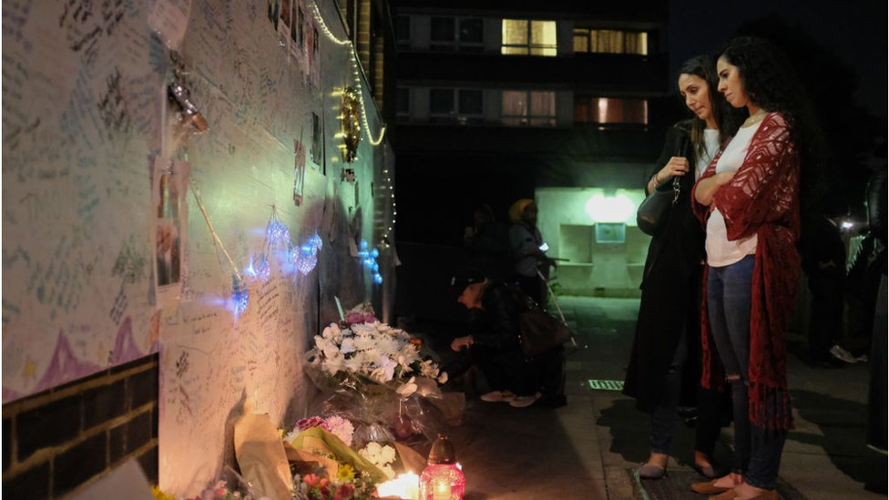 Women looking at a wall of condolence messages