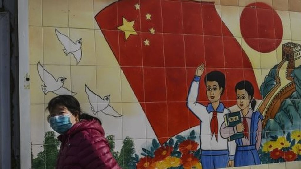 A woman wears a mask as she passes a propaganda mural in Beijing, China. Photo: 8 February 2020