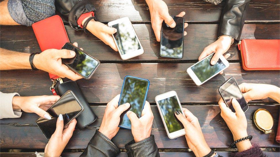 Personas con sus teléfonos móviles