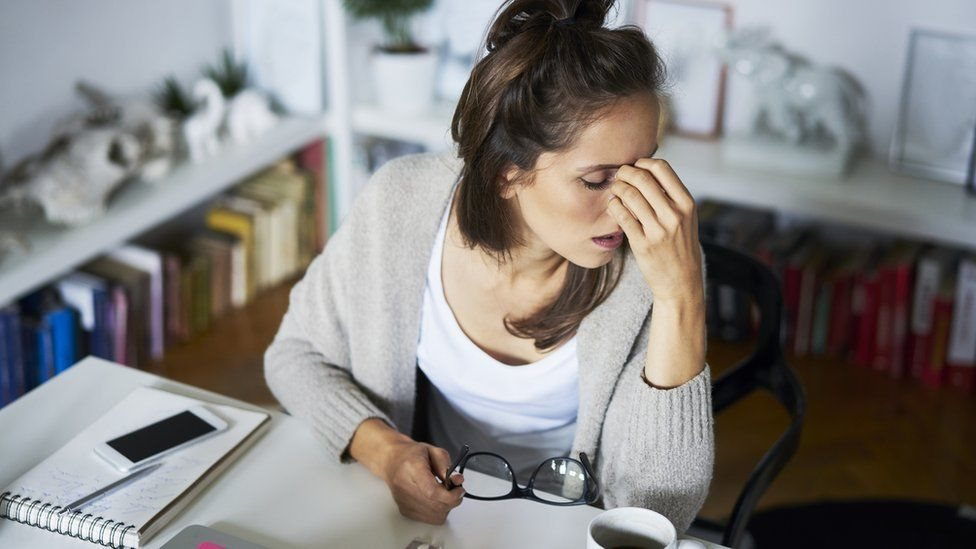 A young working woman from her desk at home holds her glasses while raising her left hand to her face as a sign of fatigue.