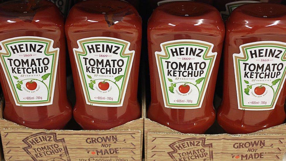 Botellas de kétchup Heinz en un mostrador.