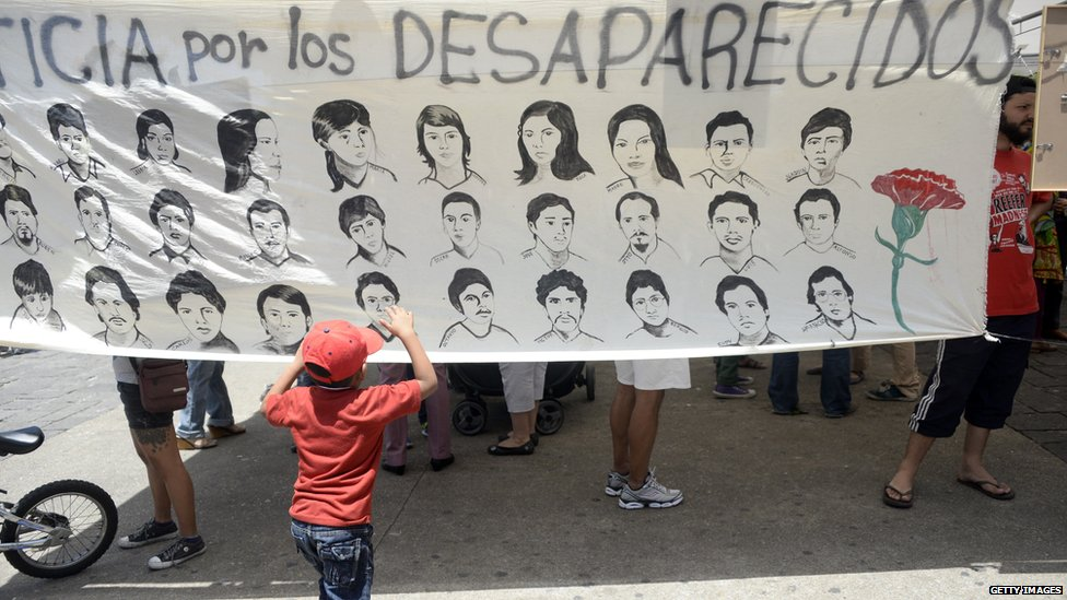 Child looking at a banner showing people who have been disappeared