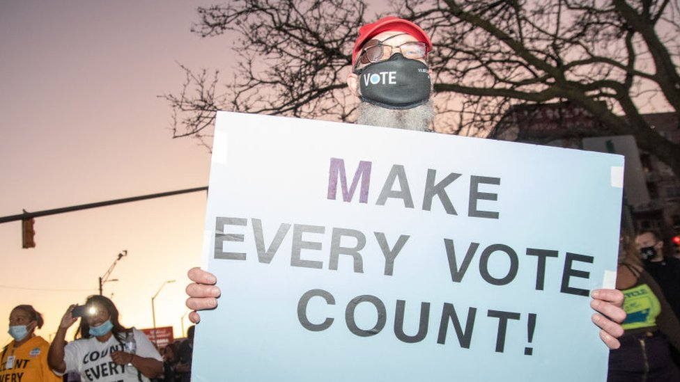 "A protester in Michigan holds up a sign that says ""Make Every Vote Count"""
