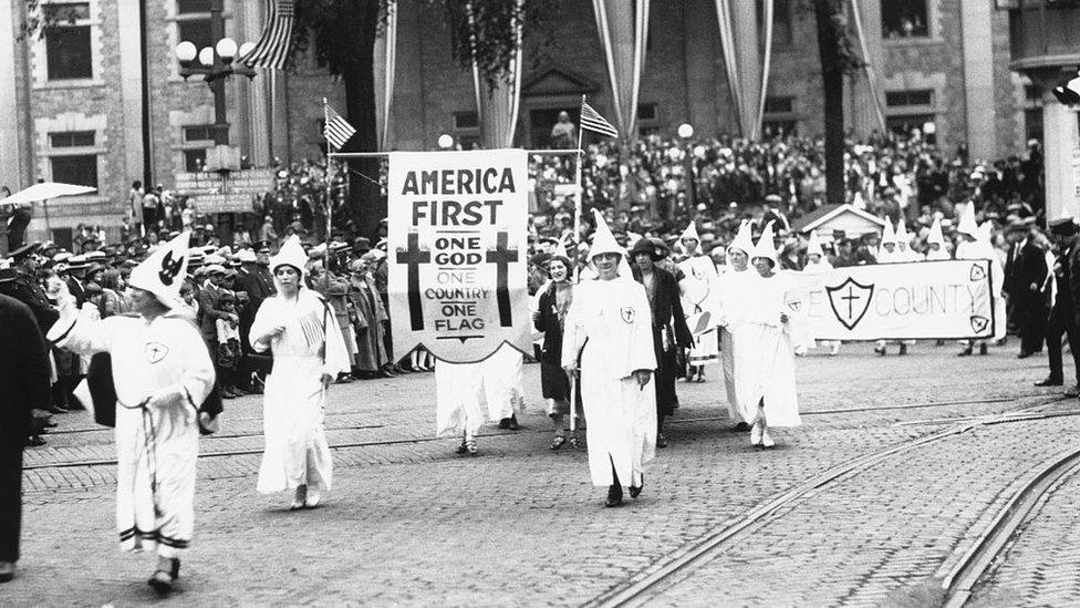 """Marcha del Ku Klux Klan con un cartel con """"America first"""" en la década de 1920."""