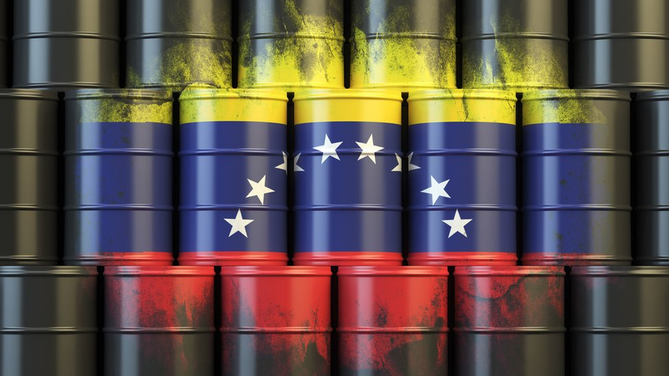 Bandera de Venezuela y barriles de petróleo.