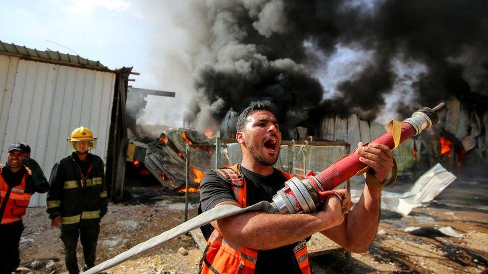 Un bombero palestino tratando de apagar el fuego en el sitio de un bombardeo.