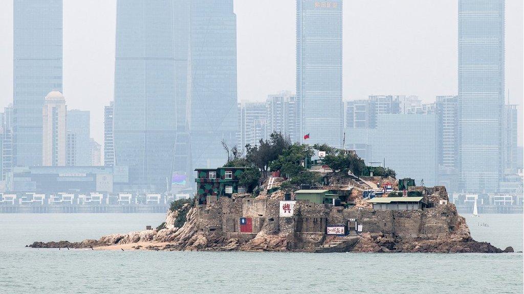 台灣金門離島小島——獅嶼。島上插有中華民國國旗,對面高樓大廈是福建廈門市(2018年4月20日資料照片)。