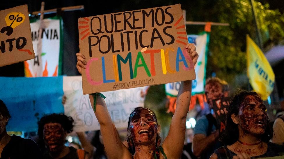 """Una joven en Río de Janeiro con una pancarta que dice """"queremos políticas climáticas"""""""
