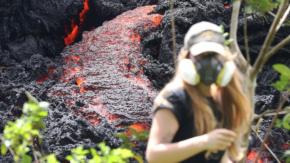 Lava flows at a new fissure in the aftermath of eruptions from the Kilauea volcano on Hawaii's Big Island as a local resident walks nearby after taking photos on 12 May 2018 in Pahoa, Hawaii