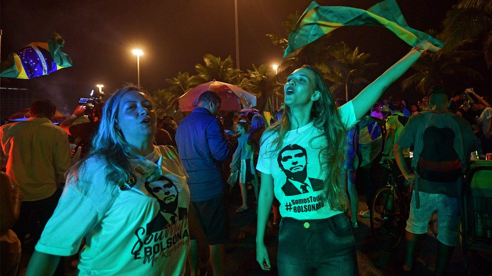 Supporters of Jair Bolsonaro celebrate outside his home in Rio de Janeiro, on October 7, 2018