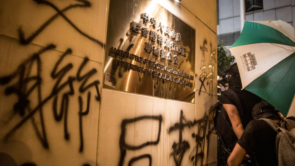 Protesters spray graffiti on the walls of the Chinese government's liaison office in Hong Kong after taking part in an anti-extradition bill march on July 21, 2019