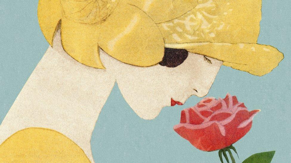 mujer oliendo unas flores