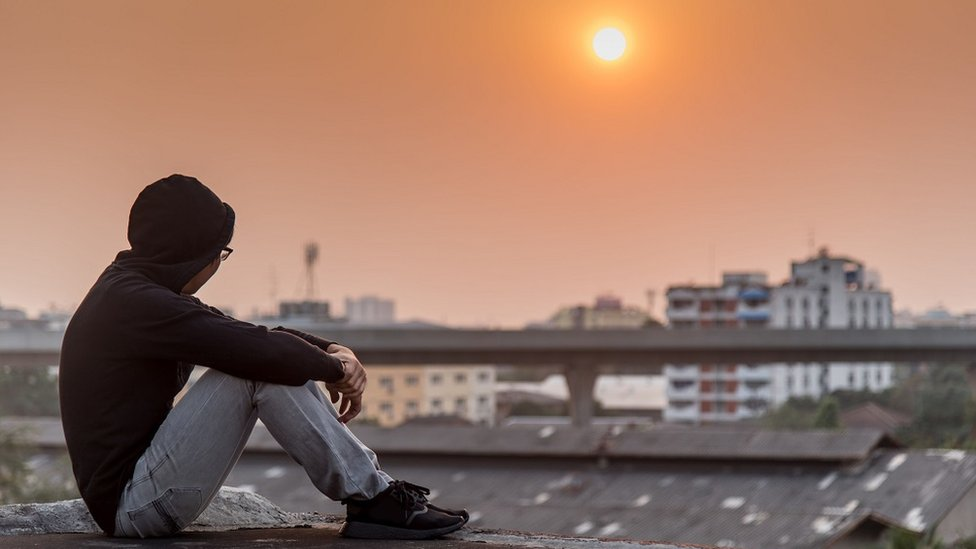 Young male sitting on a rooftop looking out