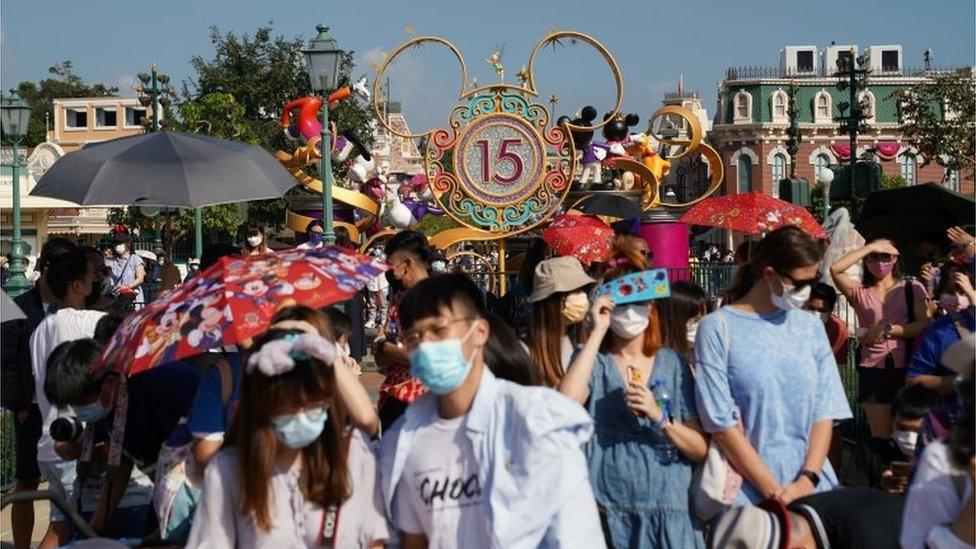 疫情期間,民眾戴口罩到訪迪士尼樂園。