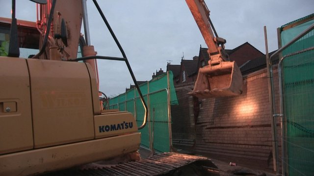 A digger dismantles part of the peace wall along the Crumlin Road