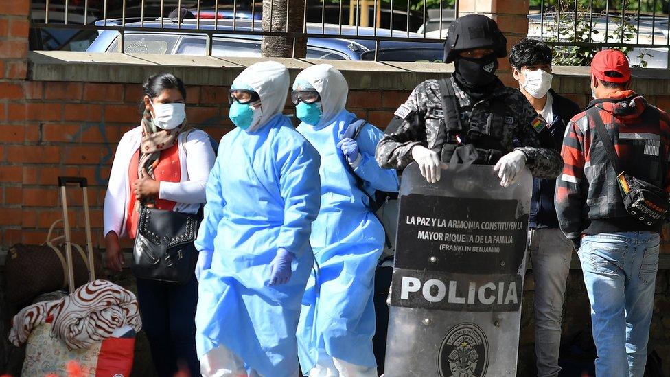 Un agente espera junto a varias personas con mascarillas y material protector en Cochabamba, Bolivia