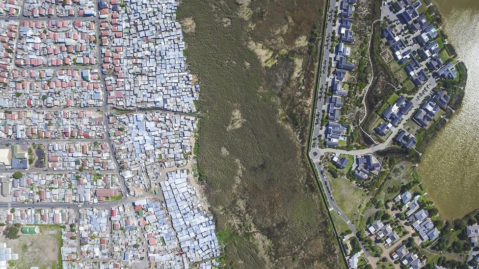 Una toma aérea del lago Michelle, una valiosa y rica finca en Ciudad del Cabo, Sudáfrica, y una comunidad más pobre, Masiphumelele.