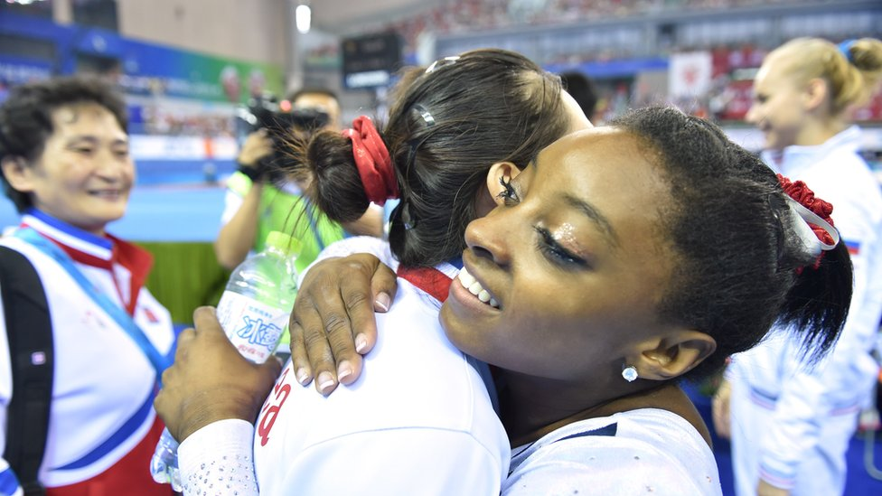 Hong Un-jong of North Korea (C) is congratulated by Simone Biles of the US (R) after their women's vault final at the gymnastics world championships in Nanning on October 11