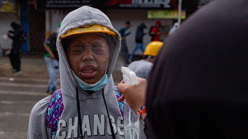 A una mujer le rocían la cara con vinagre para contrarrestar los efectos del gas lacrimógeno durante una protesta en Medellín el 2 de junio de 2021