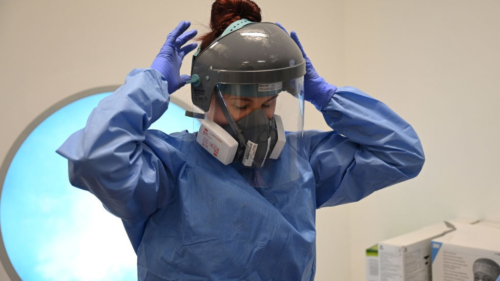 NHS medic in PPE gown and gloves