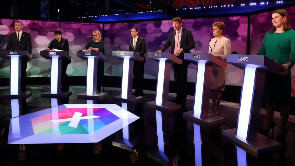 Party representatives standing at podiums during the BBC debate