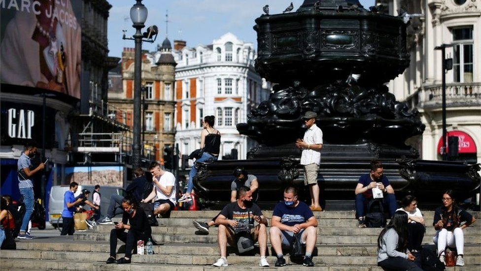 People sit on steps at Piccadilly Circus, amid the coronavirus disease