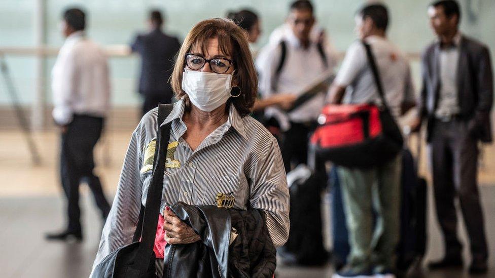 Mujer con una mascarilla en el aeropuerto internacional de Lima, Perú.