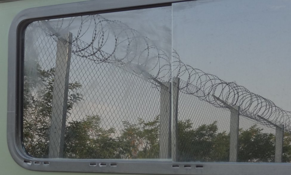 Border fence reflected in the window of a vehicle