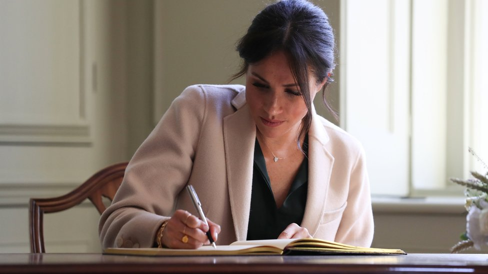 Duchess of Sussex signs the visitor book at Edes House, Chichester