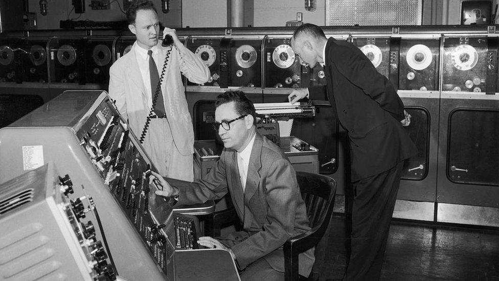 Tres hombres manejando una de las primeras computadoras.