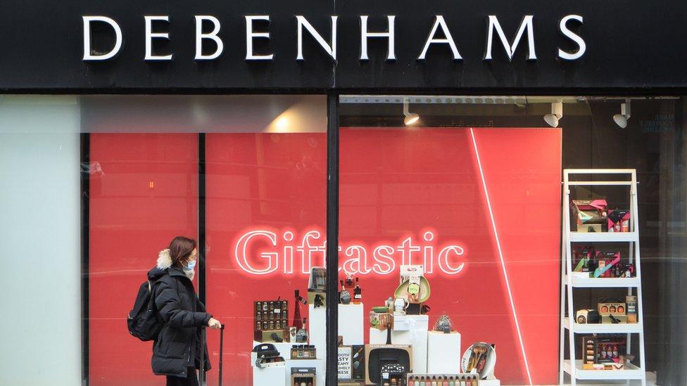 A woman walking past Debenhams
