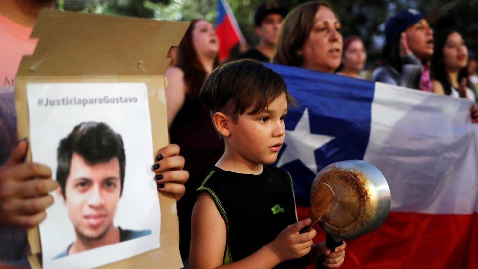 Niño con cacerola junto a un cartón con la foto de Gustavo Gativa. La Colina, Chile, 10 de noviembre de 2019.