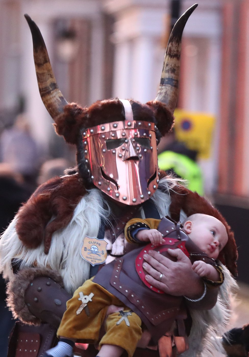 Reveller dressed as a warrior walks through Lewes carrying a baby