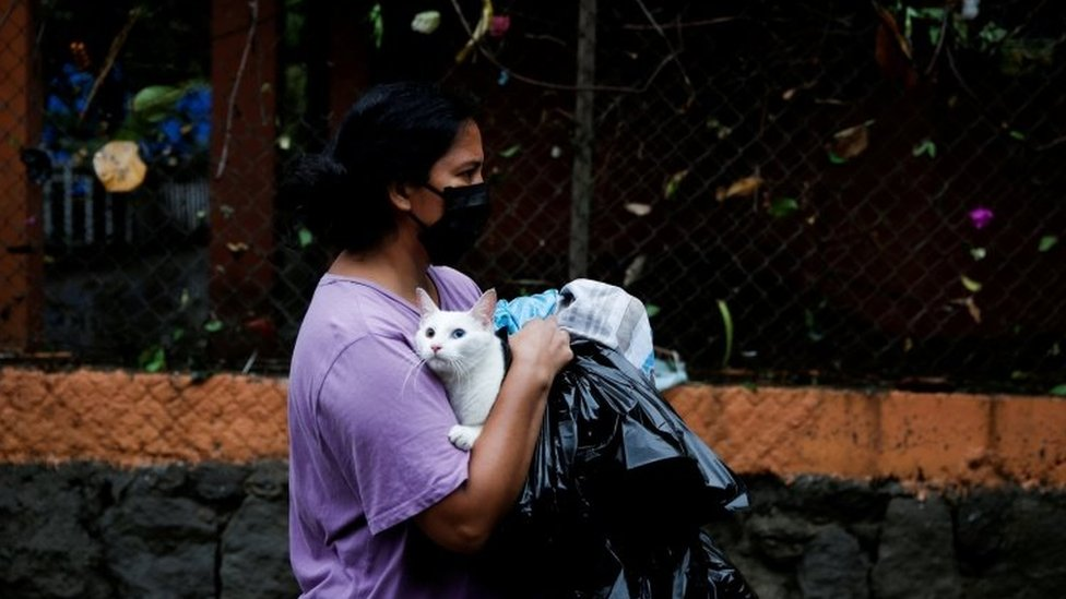 A woman wearing a face mask walks holding a cat during floods caused by Tropical Storm Amanda, in San Salvador, El Salvador May 31, 2020
