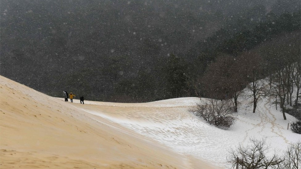 People walk on the partially snow covered Pyla sand dune after snow fall on 28 February 2018 in La Teste-de-Buch, south-west France