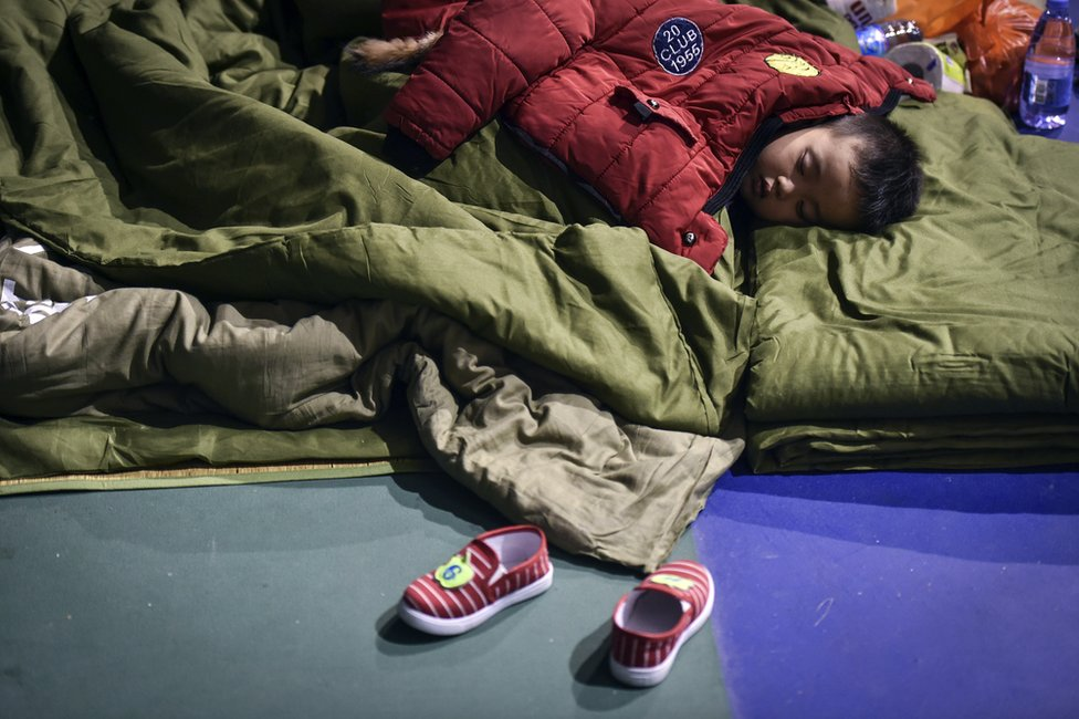 In this photo released by China's Xinhua News Agency, an evacuated boy rests at a makeshift shelter place located at a sports centre in Shenzhen, south China's Guangdong Province Monday, 21 December 2015