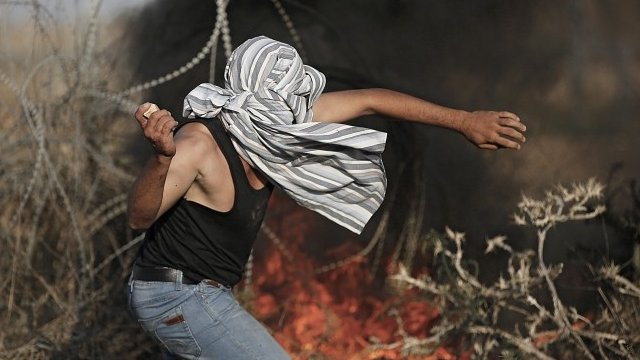 Palestinian throwing stone during Gaza clashes