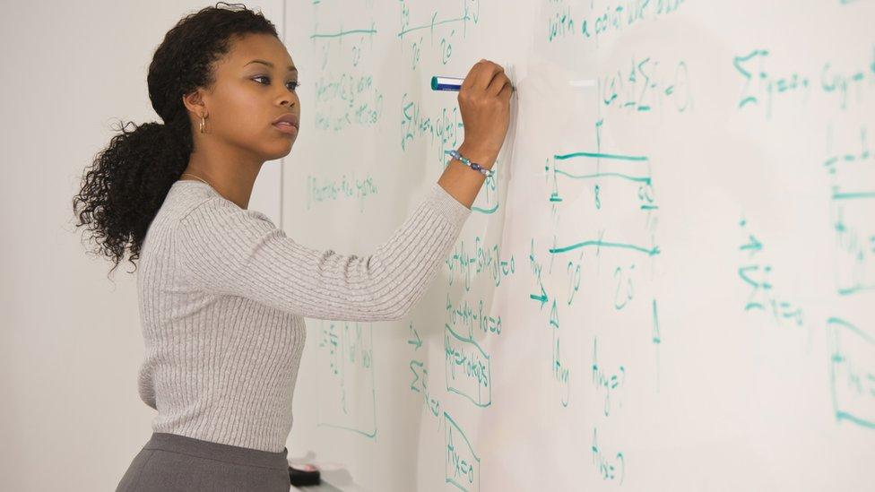 Una mujer escribe fórmulas matemáticas en una pizarra
