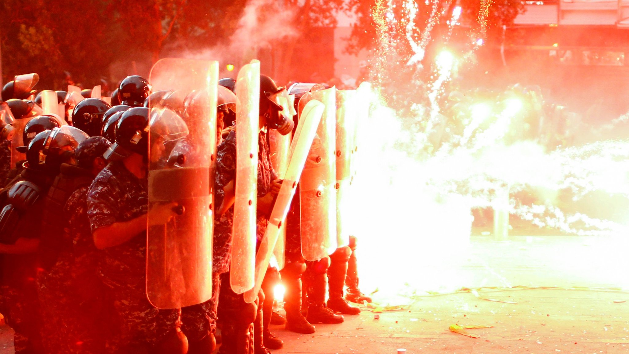 Fireworks launched by anti-government protesters hit the shields of riot police officers in Beirut on 10 August 2020