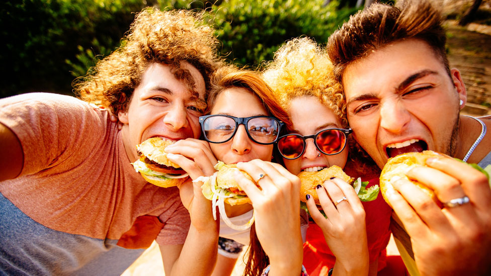 A group of young people eating hamburgers.