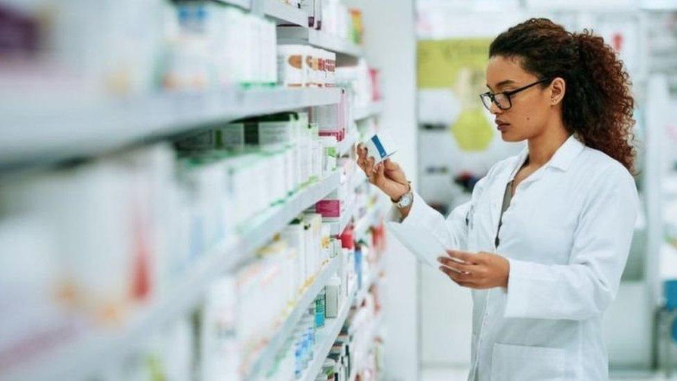 Mulher com jaleco branco checa medicamentos em prateleira