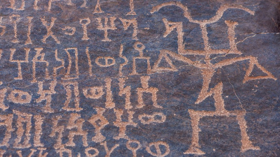 نقوش قديمة على صخرة في منطقة حمى الثقافية بالسعودية