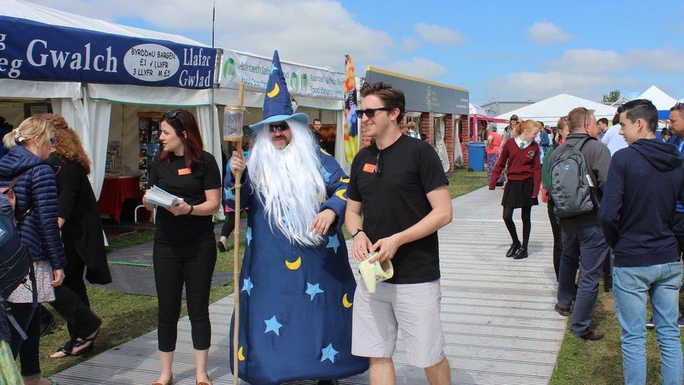 Y dewin Myrddin yn crwydro'r Maes // As if by magic, Merlin appears on the Maes