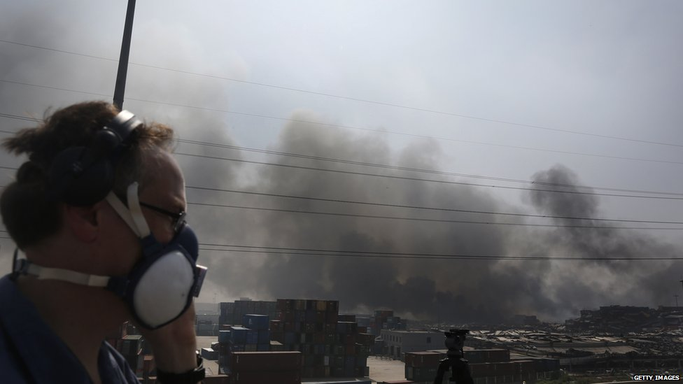 Smoke billows from the site of two explosions at Tianjin